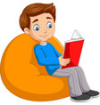 young boy reading a book sitting on big pillow vector image vector image