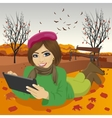 Young woman using tablet in autumn park vector image vector image