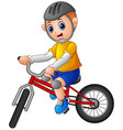 young boy riding a bicycle on a white background vector image