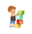 cute boy stacking up cube tower forming a true vector image vector image