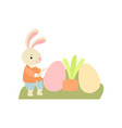 cute bunny playing with colorful eggs in garden vector image