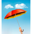 Hand holding a red and yellow umbrella against a vector image