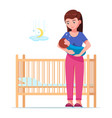 woman holding a sleeping baby next to a baby crib vector image vector image