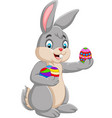easter bunny holding a decorated an egg vector image vector image