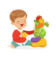 smiling little boy sitting on the floor playing vector image