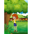 A woman with a cellphone standing under the tree vector image