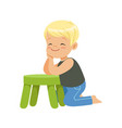 sweet smiling little boy sitting on the floor vector image
