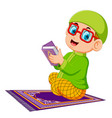 boy using red glasses is holding al quran