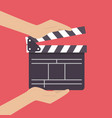 hands holding movie clapper vector image