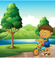A kid at the riverbank playing with his bicycle vector image vector image