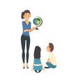 Female teacher standing beside chalkboard and