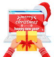 hands with gift box laptop is in santa claus hat vector image