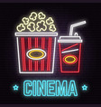 Retro neon cinema sign on brick wall background