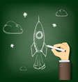 human hand drawing chalk on a blackboard a rocket vector image vector image