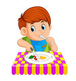 a young boy sitting while enjoy having breakfast vector image
