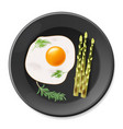 fried eggs with asparagus on black plate vector image