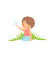 cute happy boy sitting on green meadow and playing vector image vector image