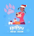 african american woman in santa hat holding cute vector image