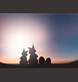 silhouette of easter bunnies against a sunset sky vector image vector image