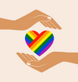rainbow painted heart in open palms vector image